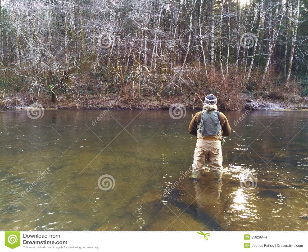 Man fly fishing in cold winter weather stock images for Fishing in cold weather