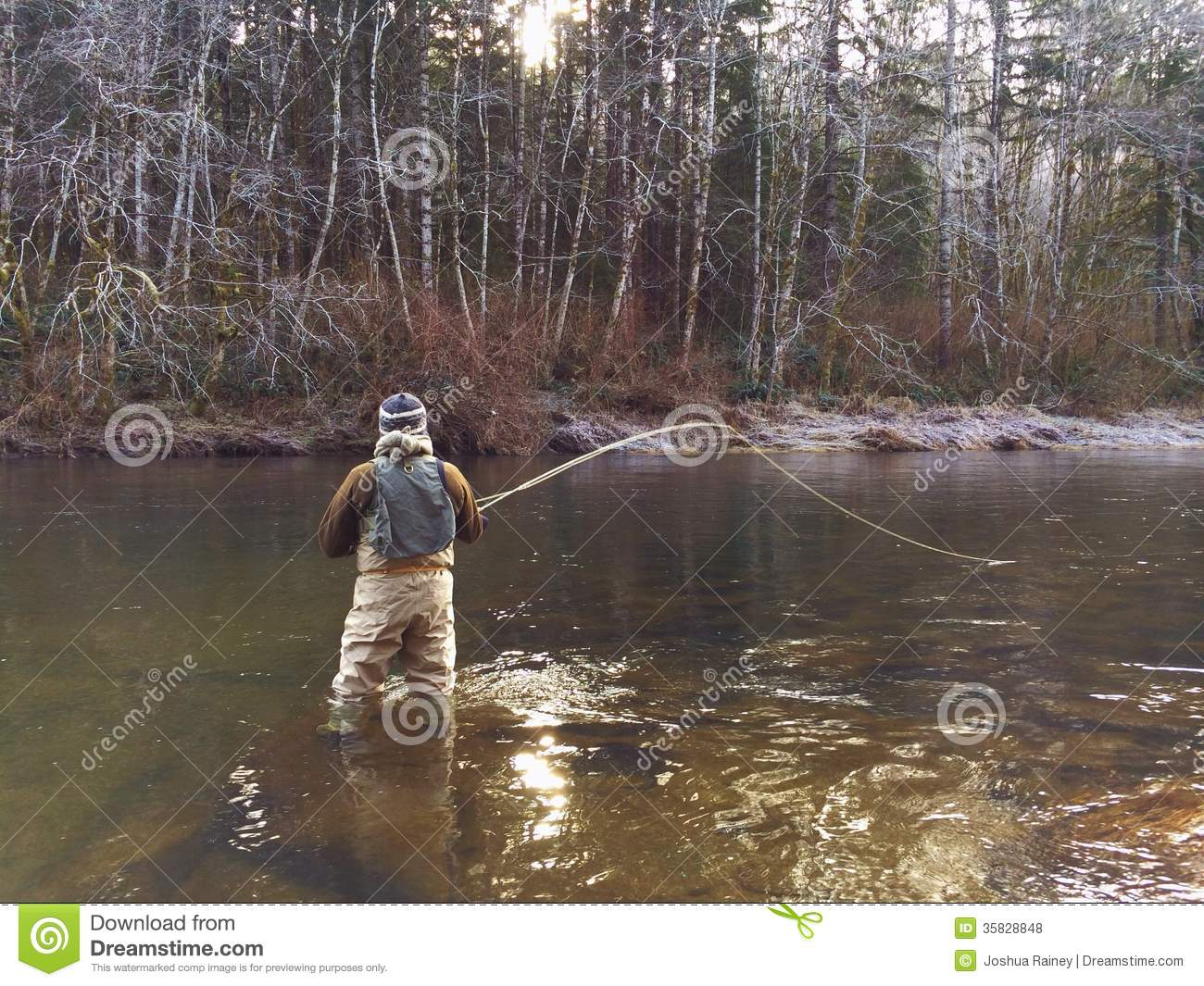 Man fly fishing in cold winter weather royalty free stock for Fishing in cold weather