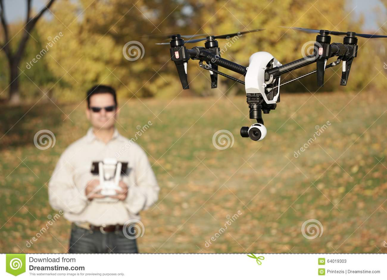 Man Flying A High-Tech Camera Drone (Fall Trees & Leaves in Background)