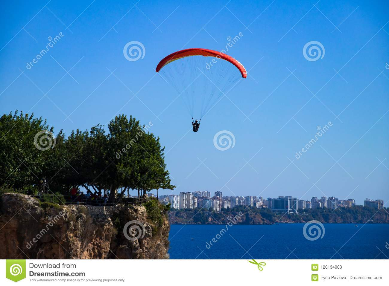 A man is flying on a paraglider