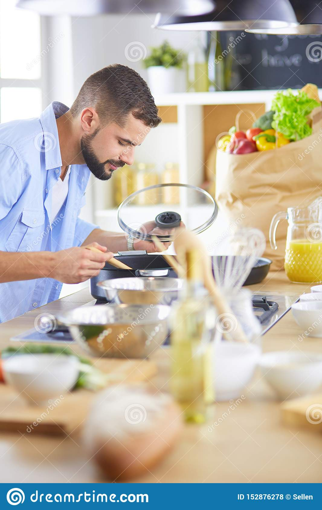 Man following recipe on digital tablet and cooking tasty and healthy food in kitchen at home