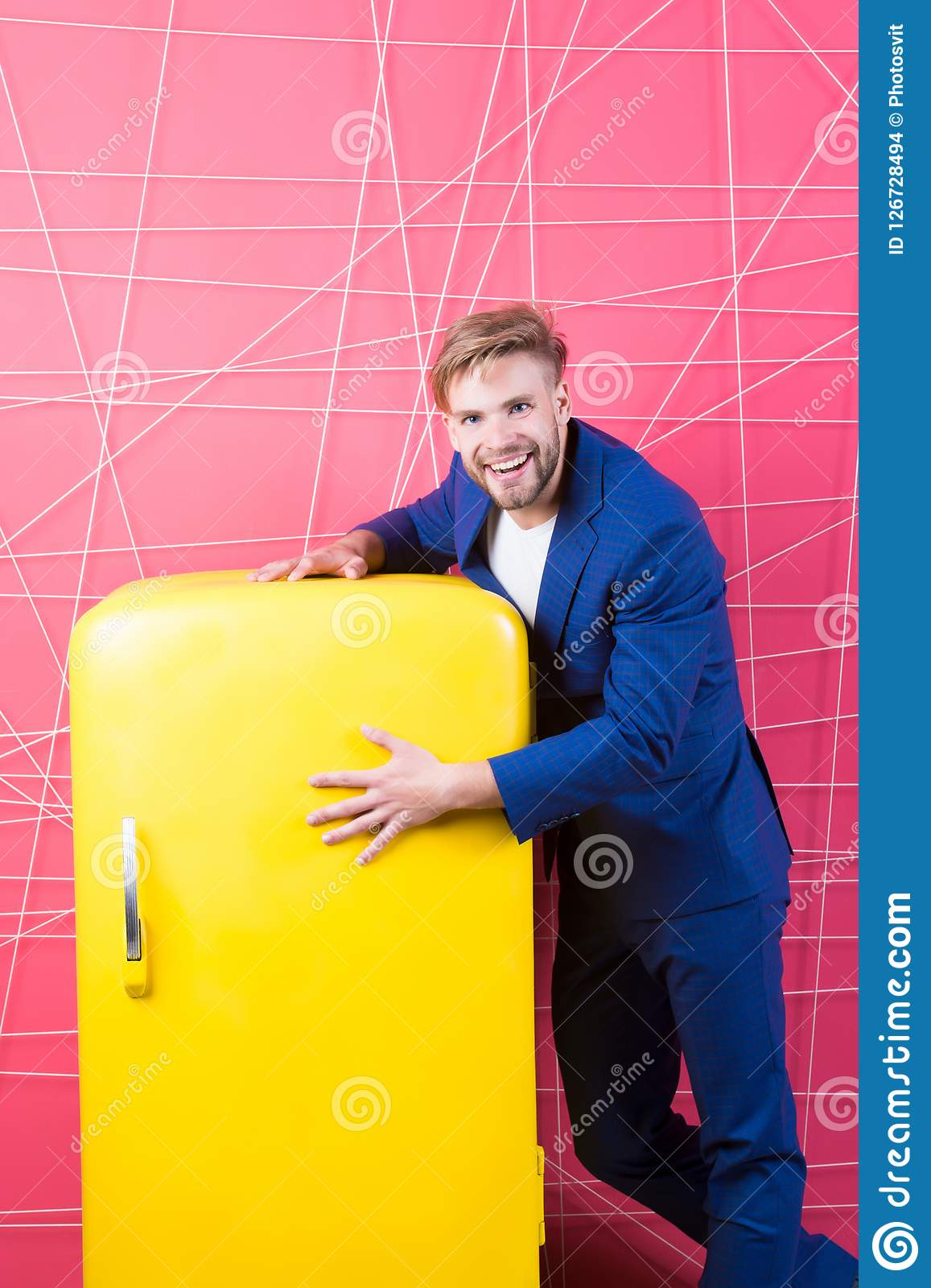 Man formal elegant suit stand near retro vintage yellow refrigerator. Vintage household appliances. Bachelor hungry guy. Think what eat near fridge. Bright Stock Images