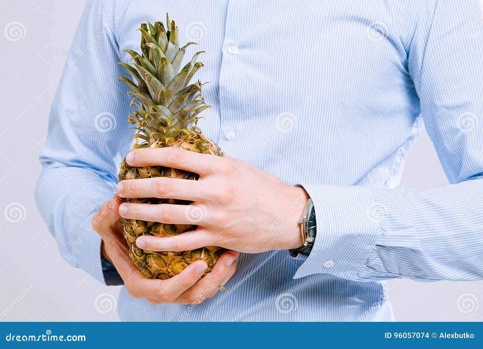 Man& fort x27 ; les mains de s dans une chemise tiennent un ananas
