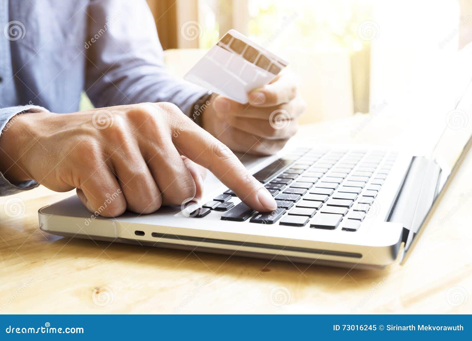 Man genom att använda bärbara datorn och mobiltelefonen till online-shopping och betala vid kreditkorten