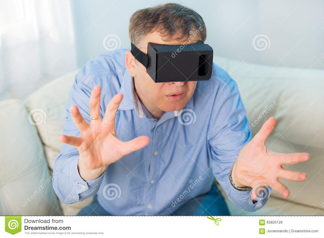 0dde47d0dc9 Man getting experience using VR-headset glasses of virtual reality at home