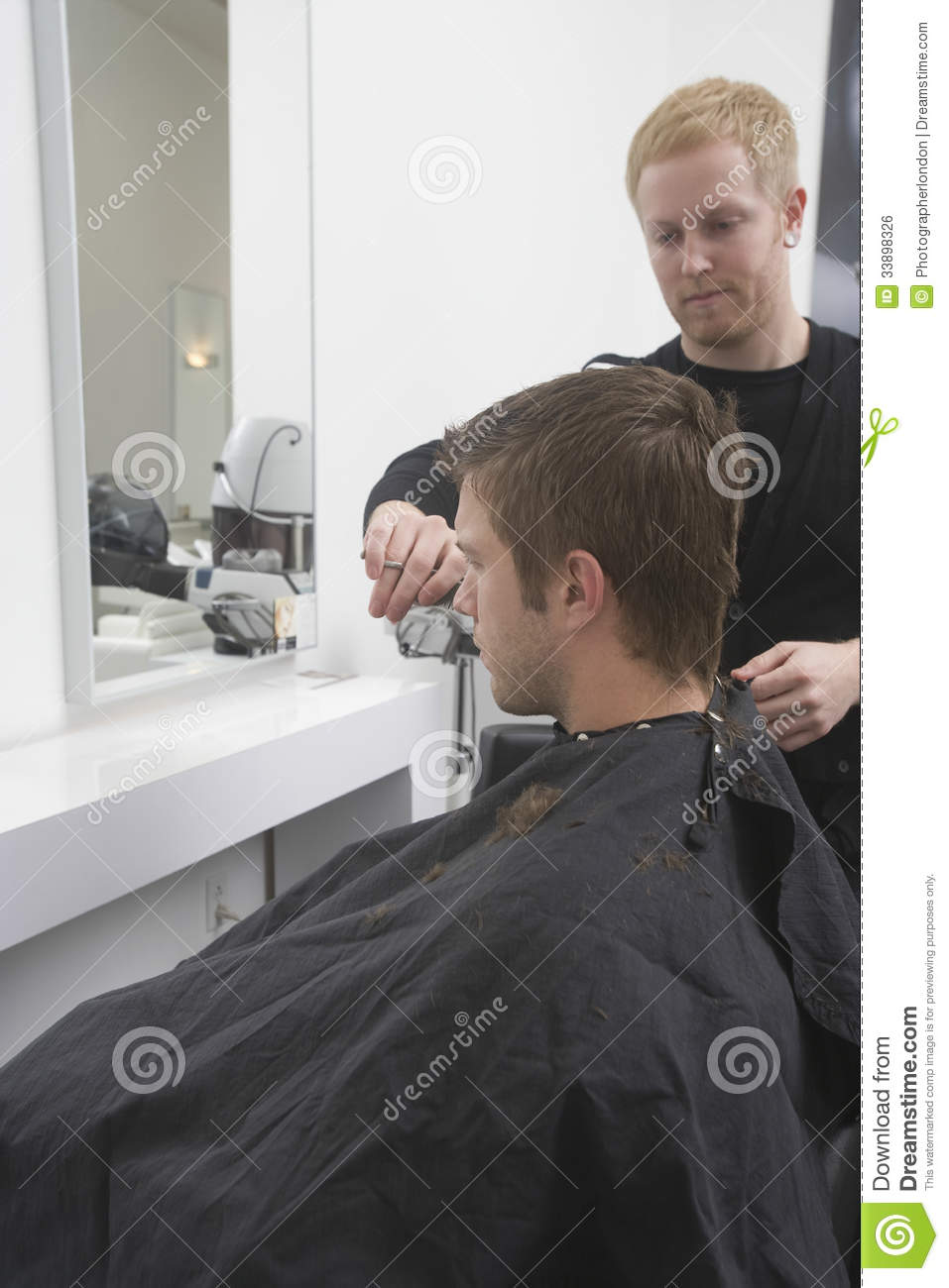 Young men getting an haircut from hairdresser in hair salon.