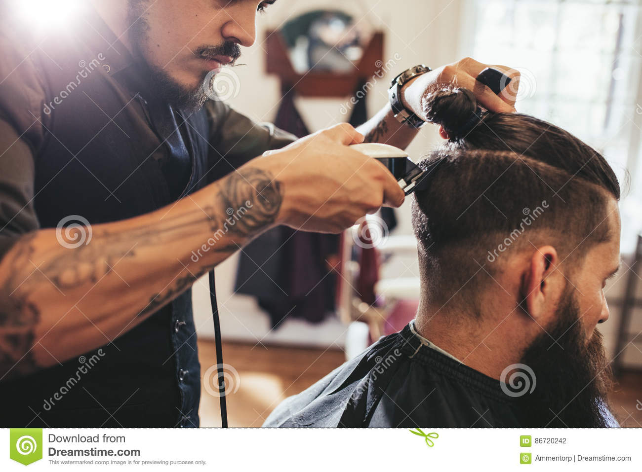 Man getting trendy haircut in barber shop