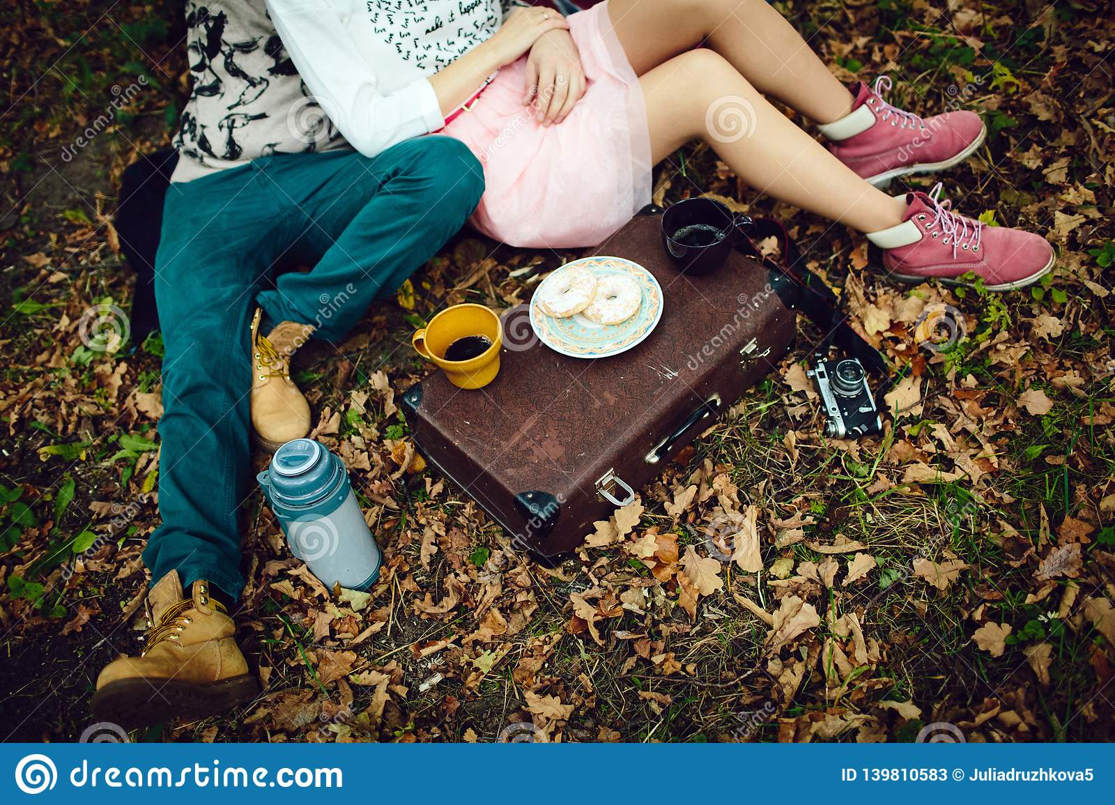 A man and a girl lying on a blanket on a winter picnic on Valentine`s day in the woods and drink tea. Top view, flat layout