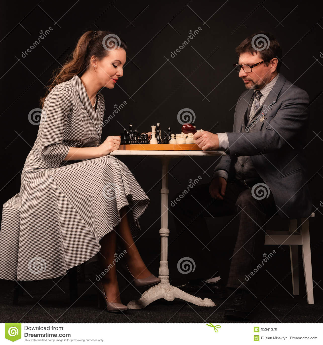 A man with a girl plays chess and smokes a pipe on a dark background