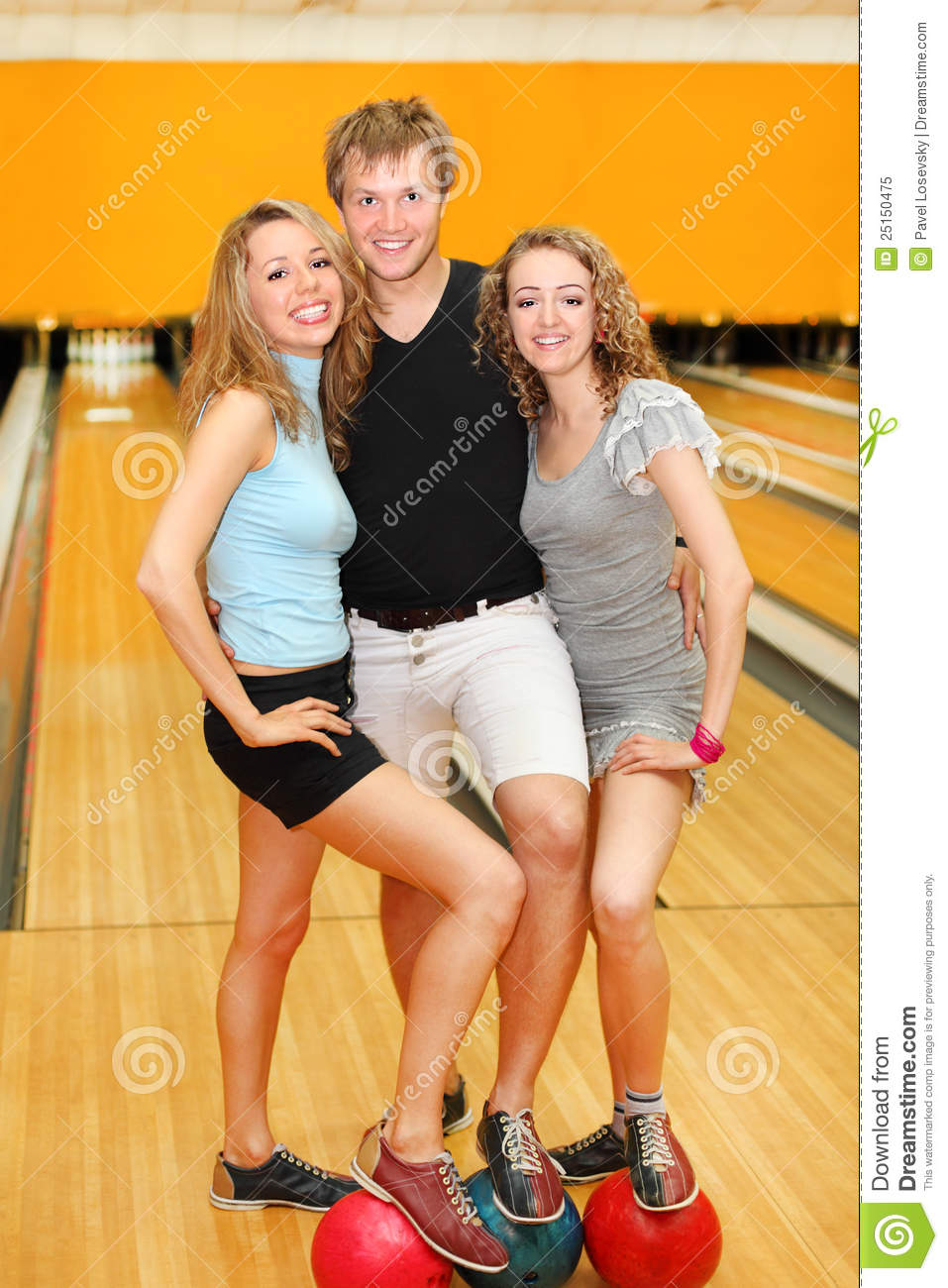 Man And Girls Put Feet On Balls In Bowling Club Stock