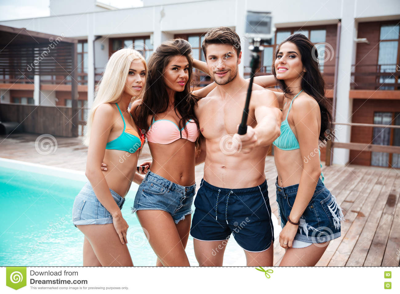 f432d8c623cee Handsome young men and three girls taking selfie with smartphone and selfie  stick standing near swimming pool