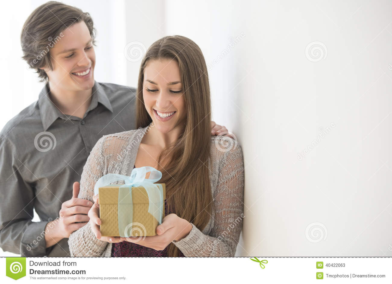 Happy Young Men Giving Birthday Gift To Women At Home