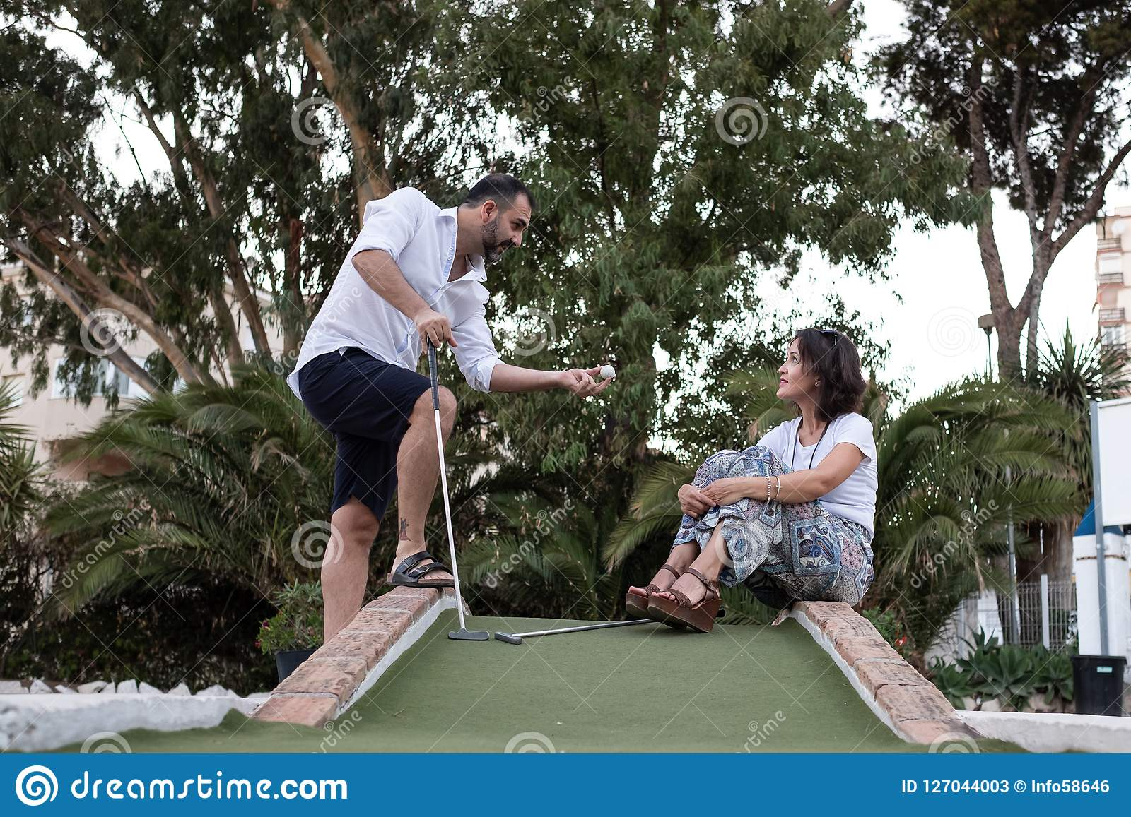 Man giving golf lesson to a woman