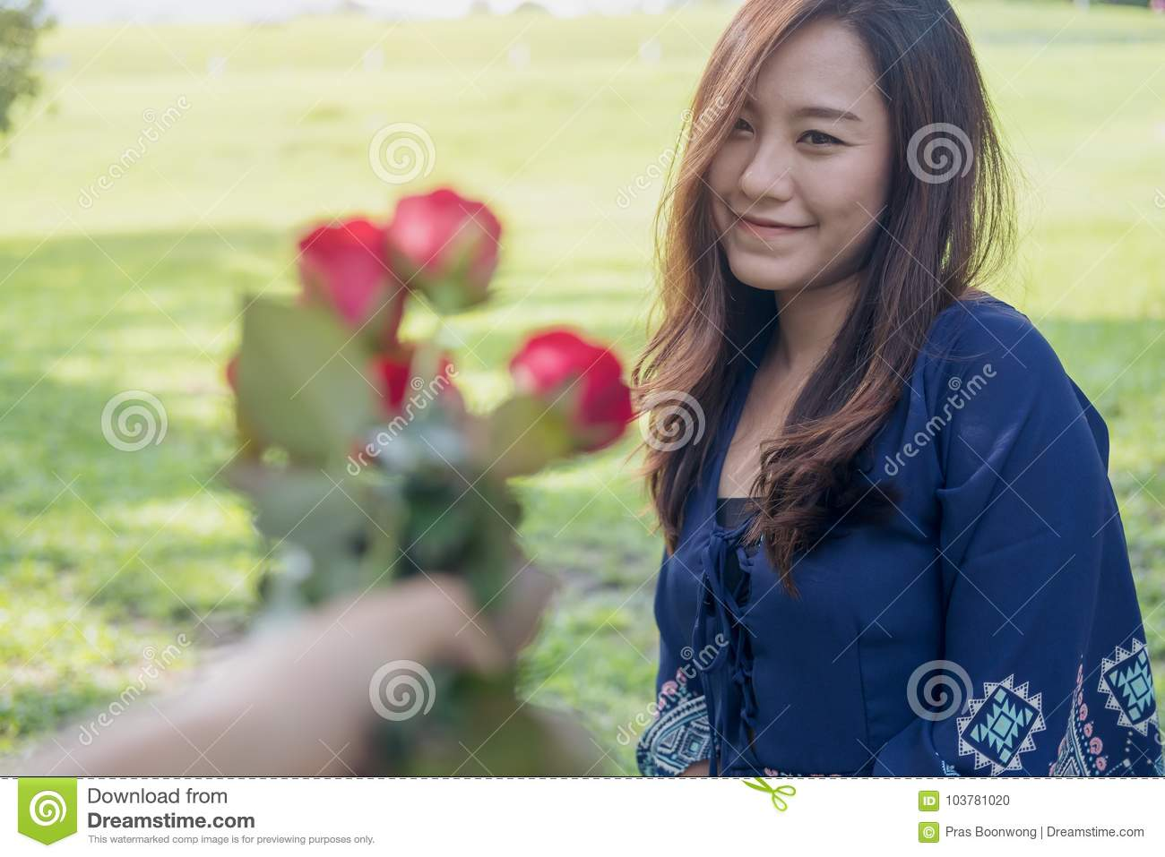 a man giving red rose flowers to asian girlfriend on valentine`s day