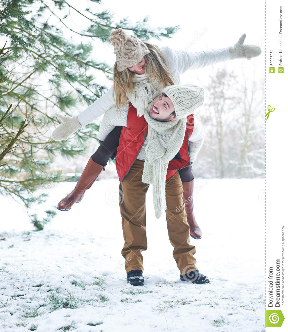 Man Giving Woman Piggyback Ride In Winter Stock Image