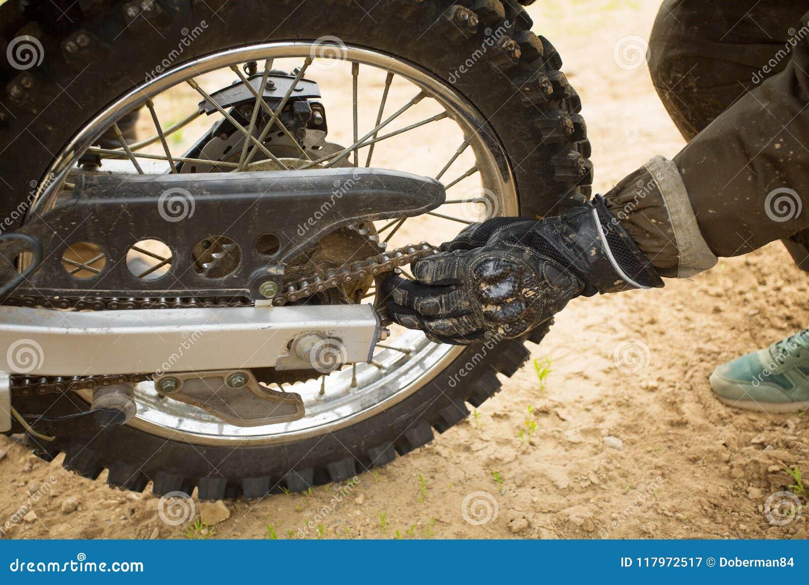 Man In Gloves Adjusting Chain On Rear Motorcycle Wheel