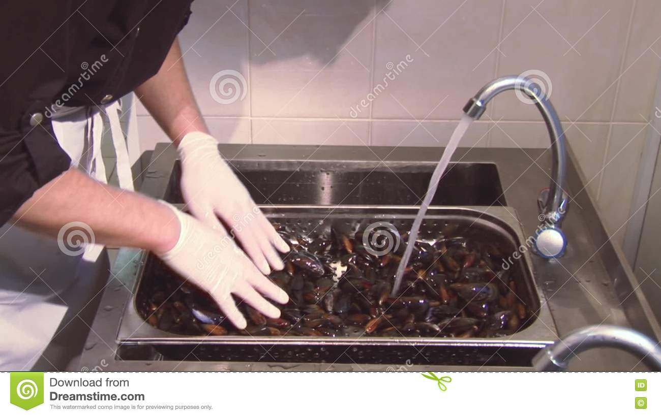 Restaurant Kitchen Gloves man in gloves mixing cleaned mussels under jet of clean water in