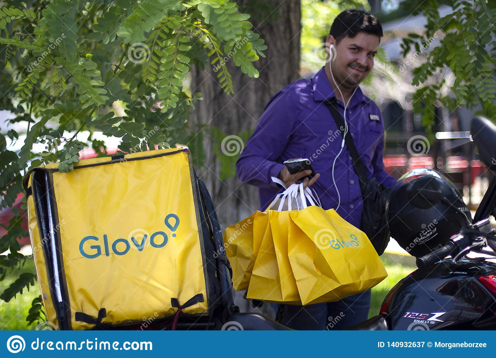 Man with Glovo bags working at food delivery service