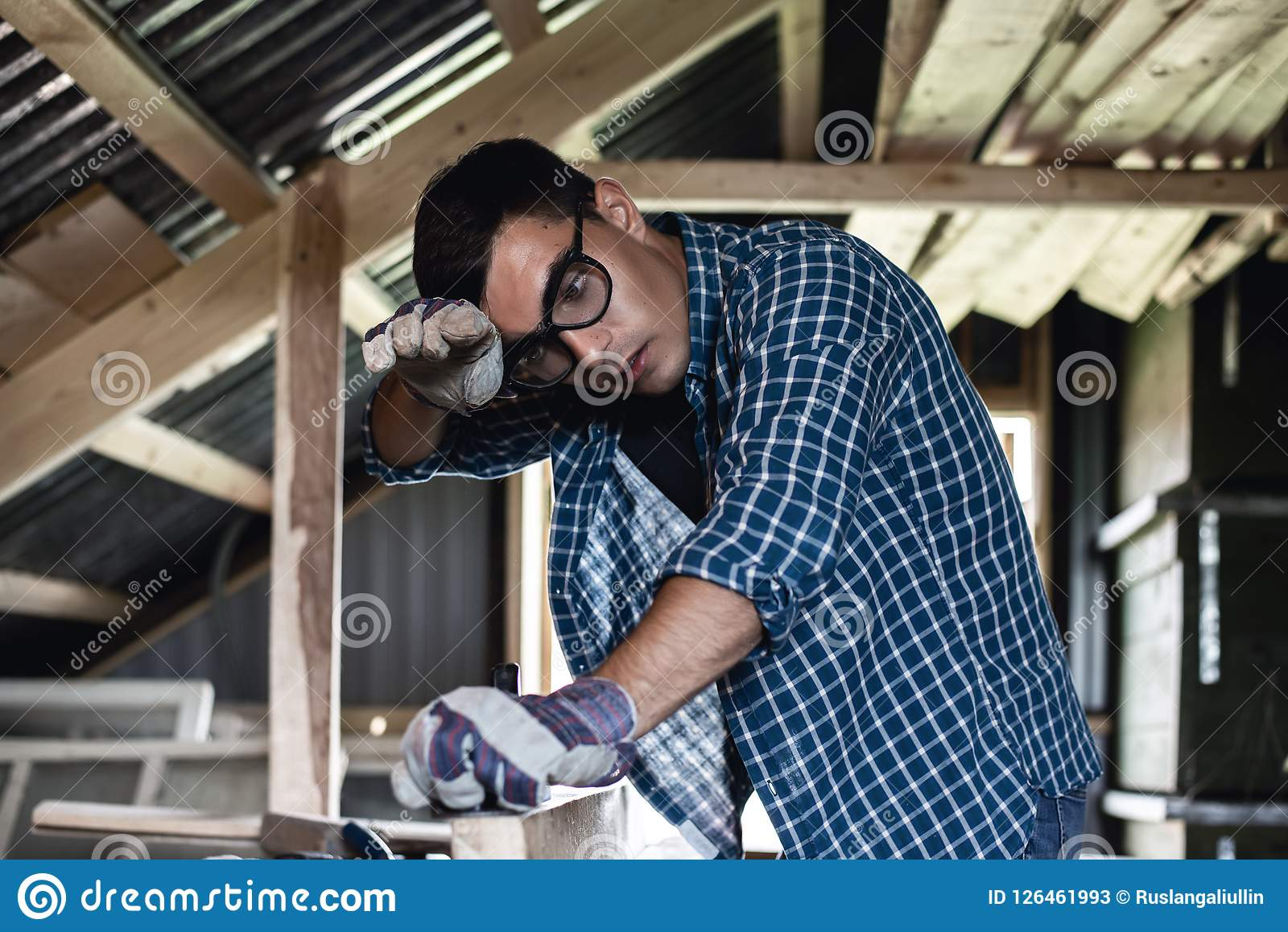 Man in goggles and wipes his forehead from sweat when handling wooden boards planer, heavy manual labor, handyman