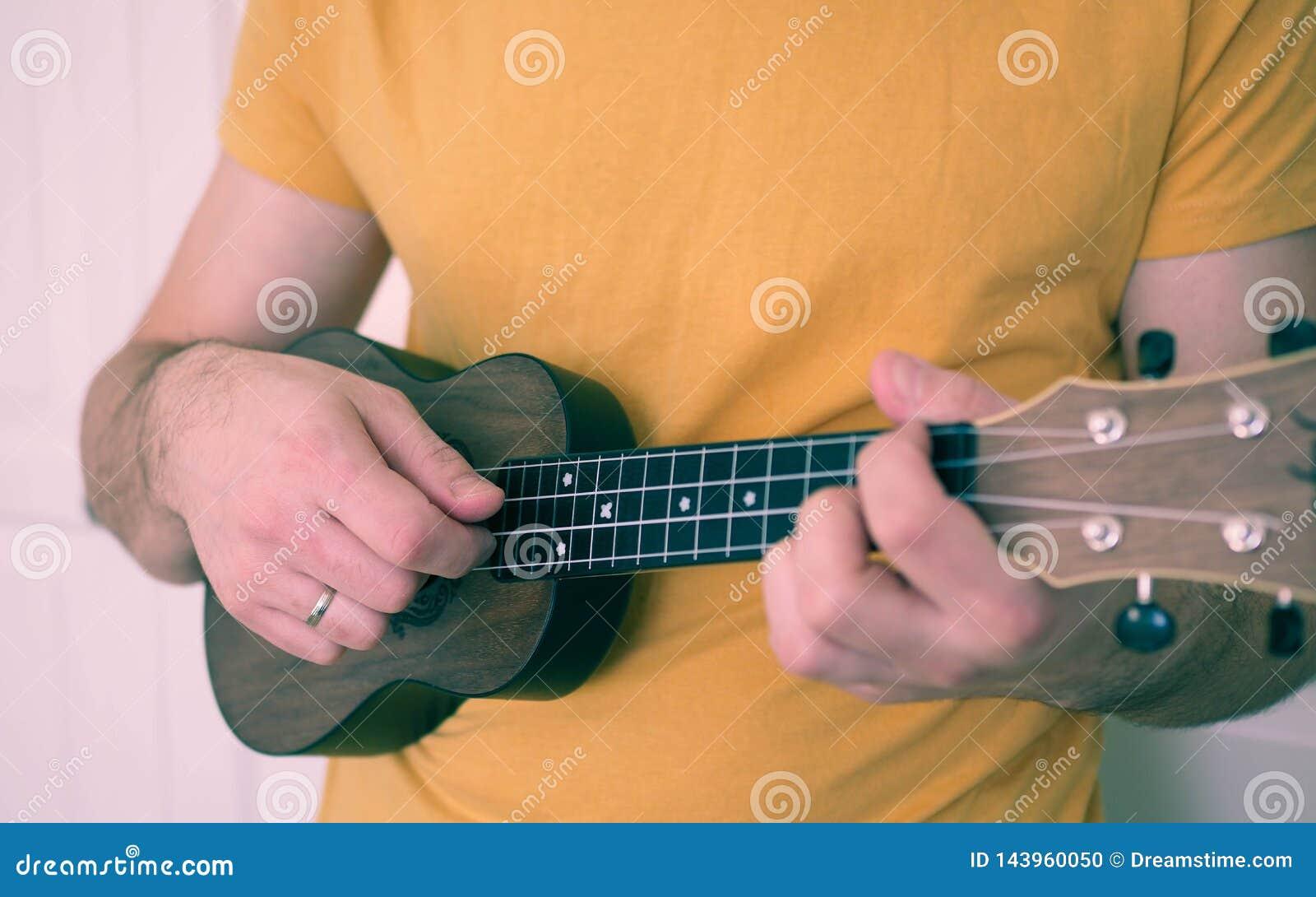 Man grabben som spelar ukulelet