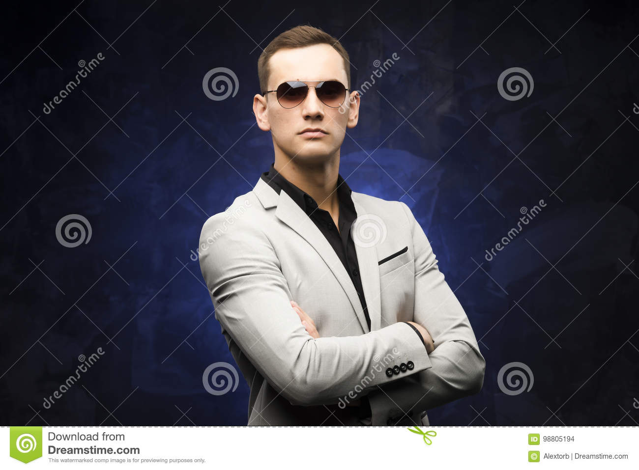 12d58890751e Man In A Gray Suit And Sunglasses On A Blue Background. Stock Photo ...