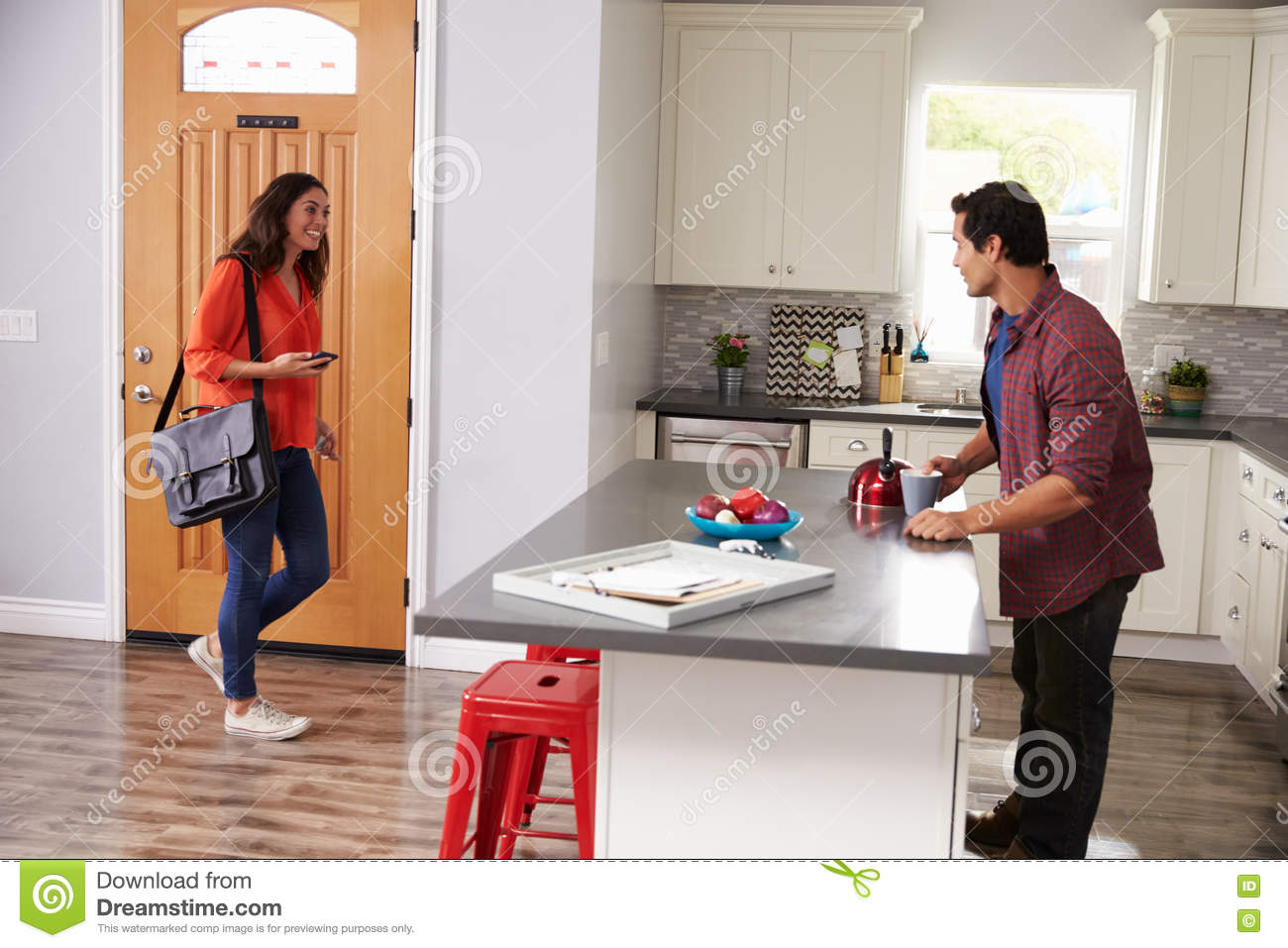 Woman Greeting Man Returning Home From Work Stock ...