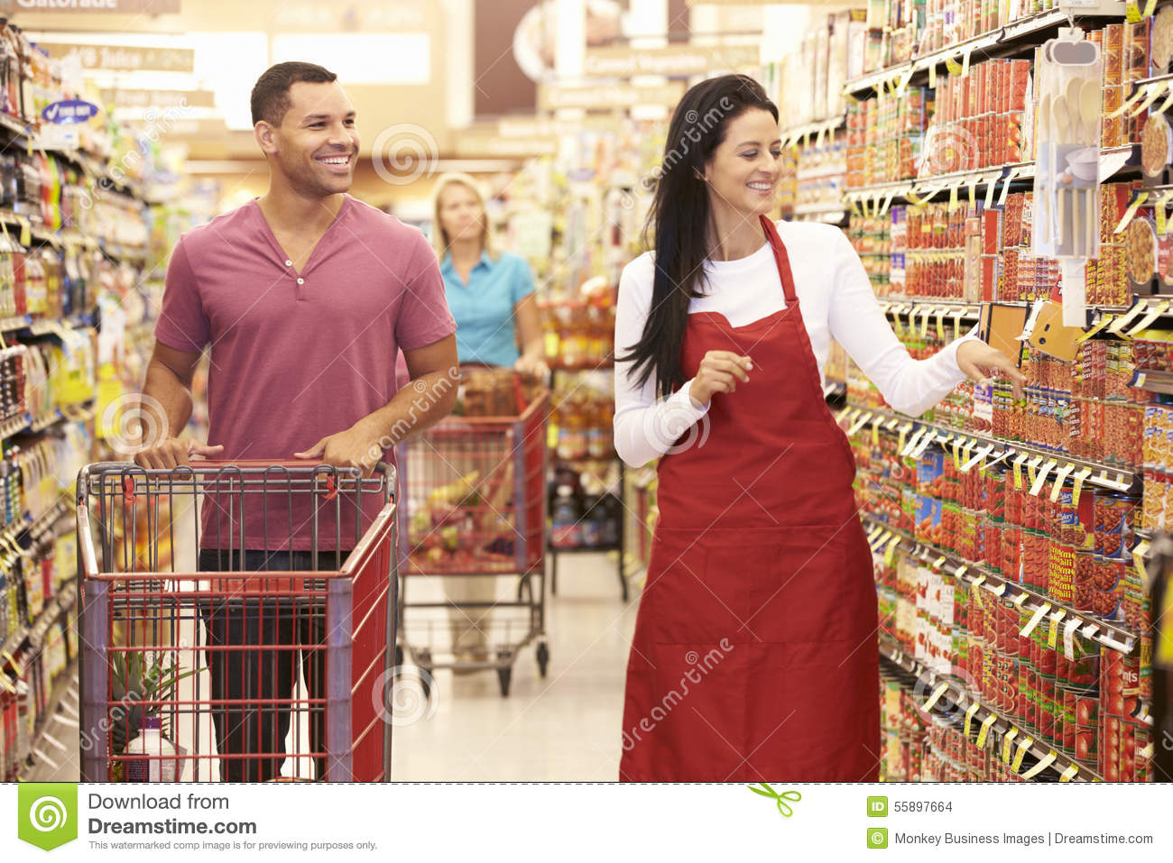 assistant in grocery shop greeting customers stock photo image man in grocery aisle of supermarket s assistant stock images