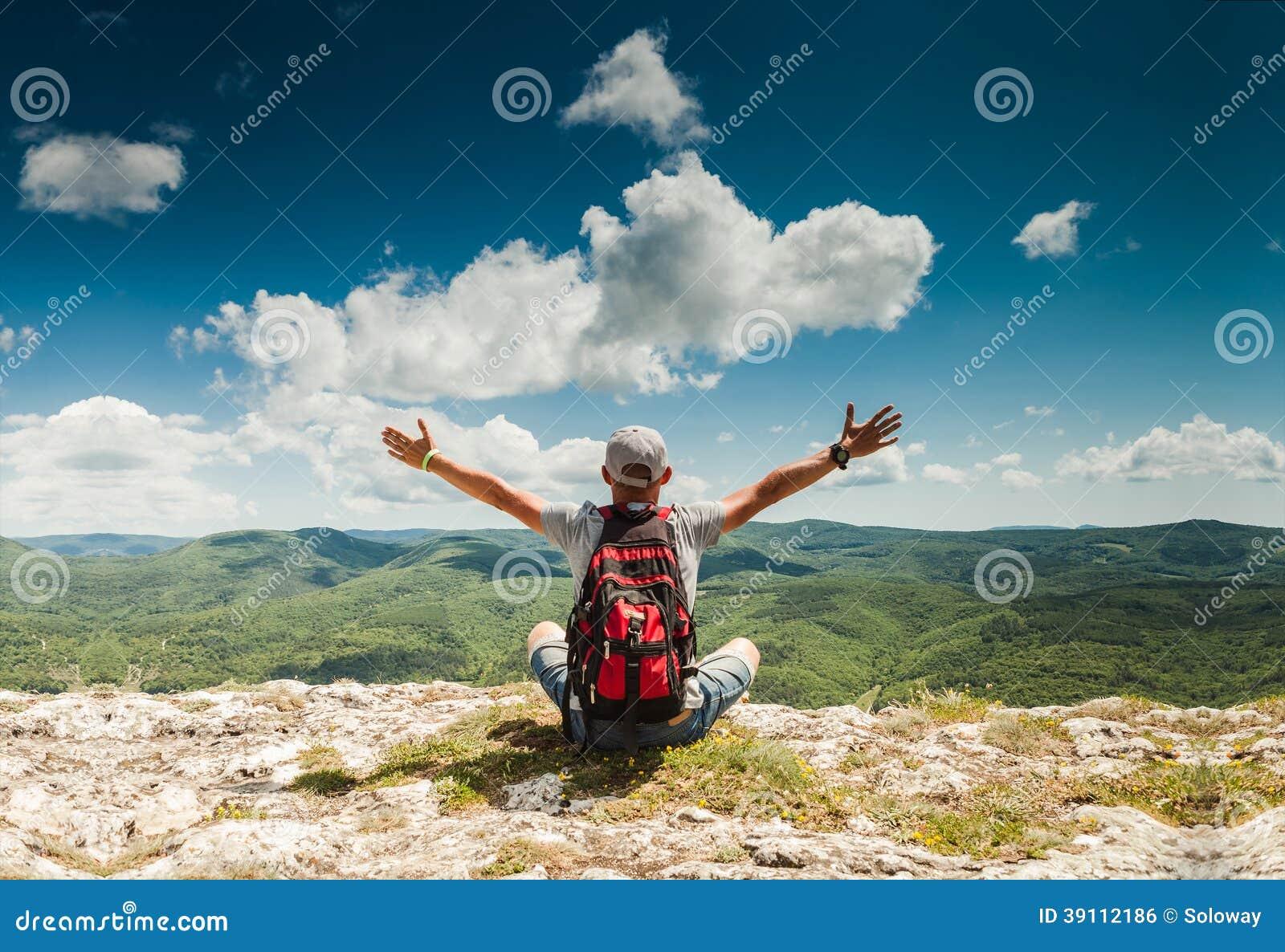 Man hälsningnaturen på överkanten av berget