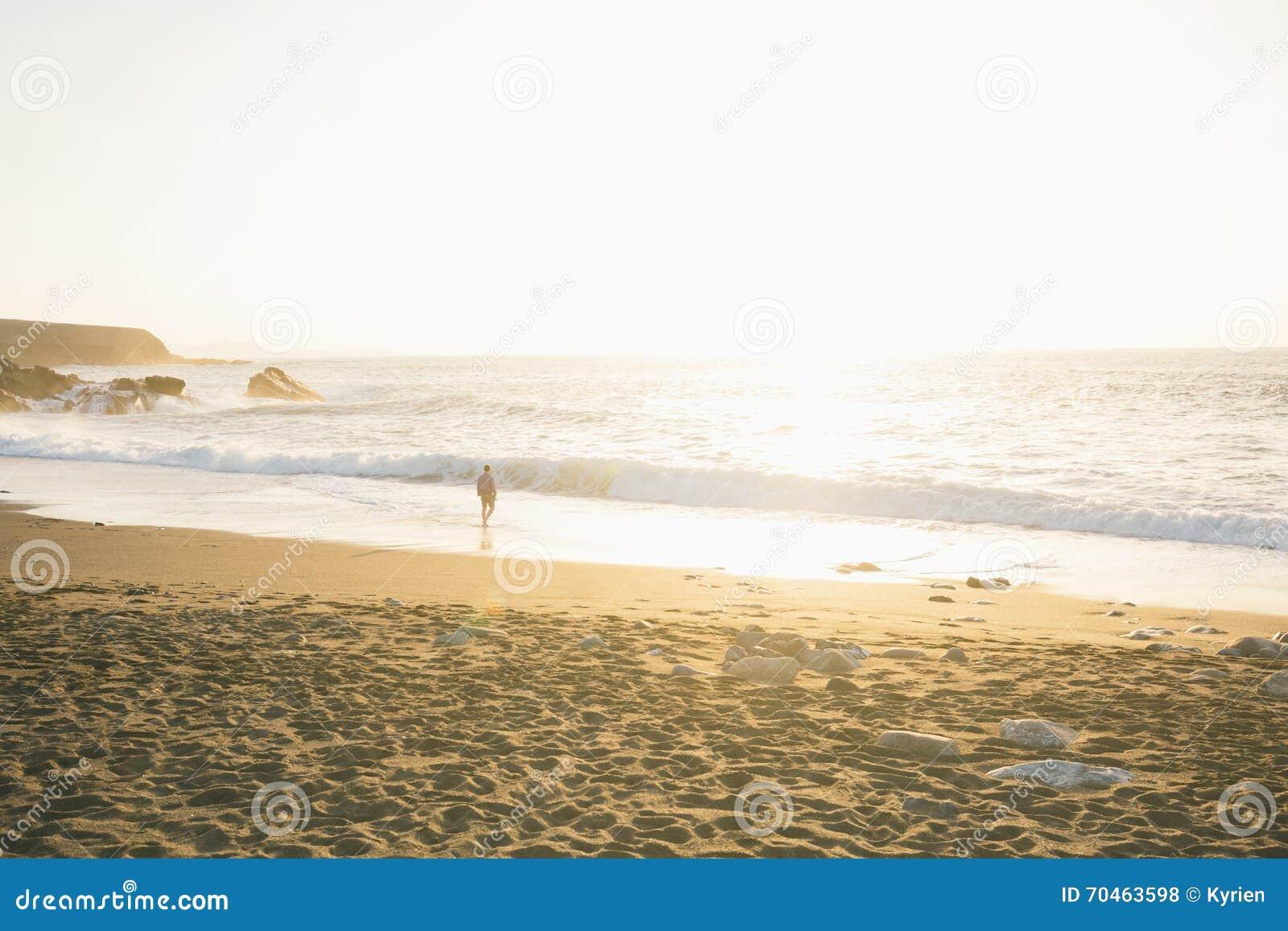 Man hänsynsfullt och ensamt gå på stranden i en fjärd