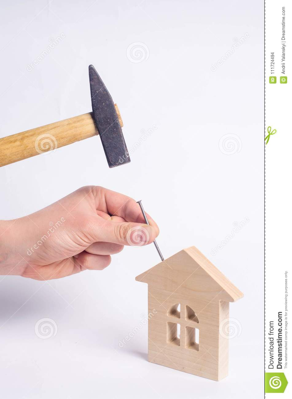 The House Of Hammer man hammers a nail with a hammer in a miniature wooden house