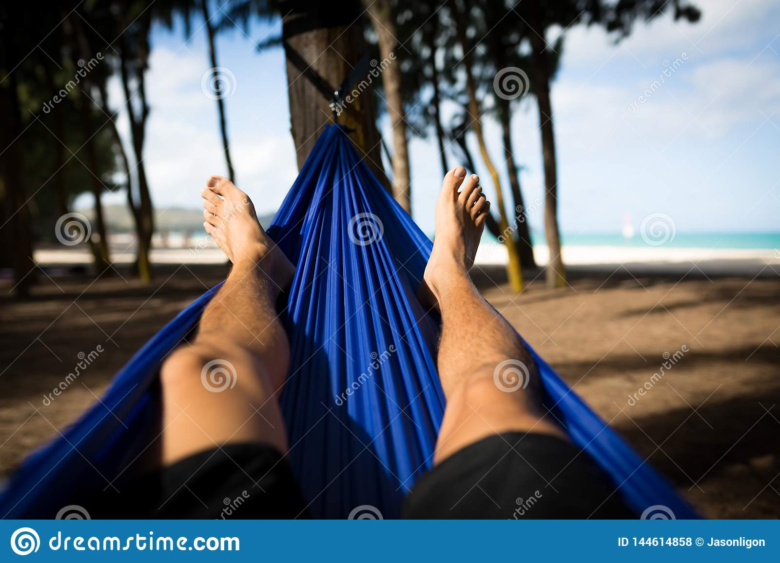 Man in Hammock Faces Beach with Happy Feet