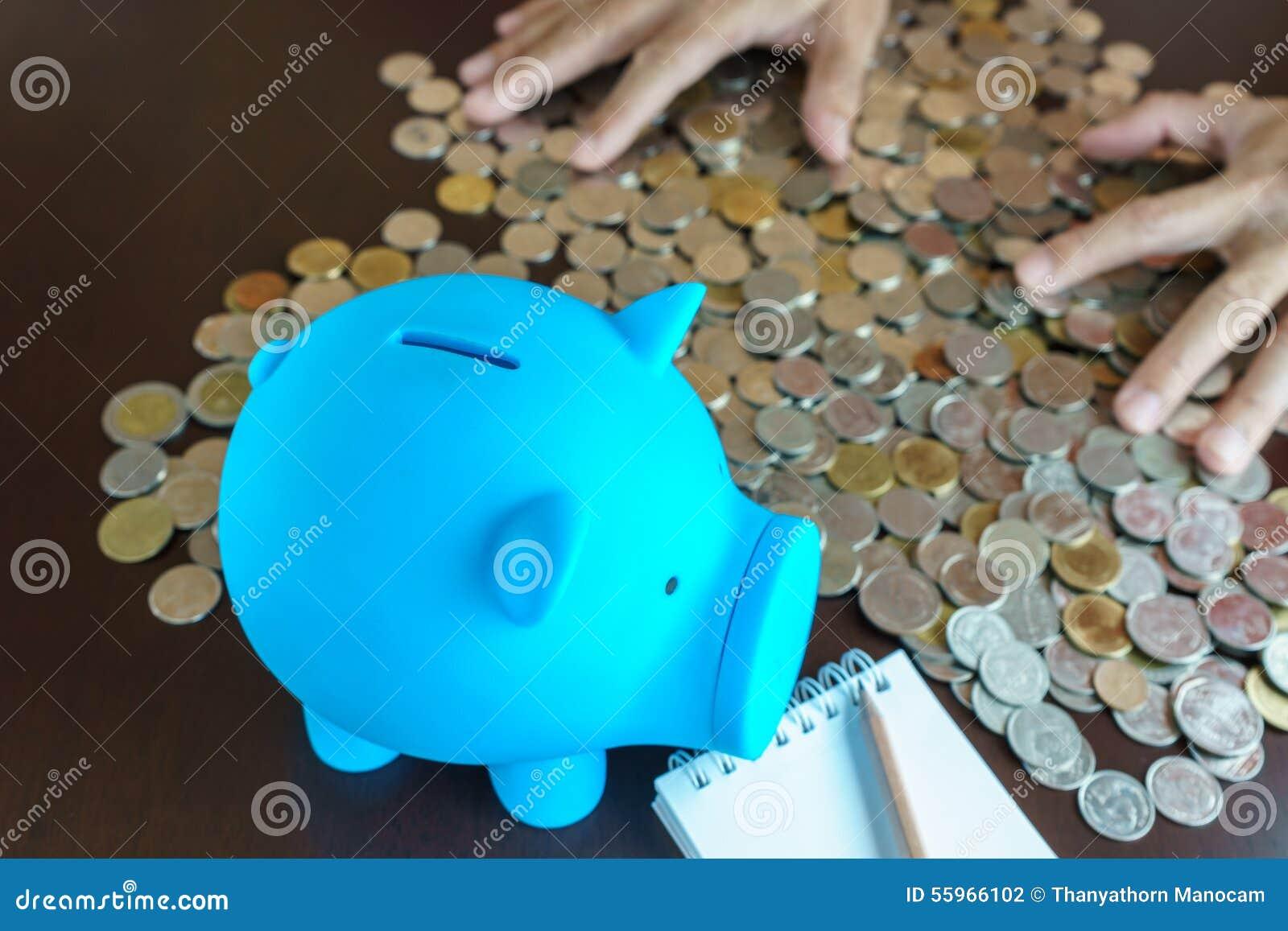 Man hand collect the money coin into blue piggy bank