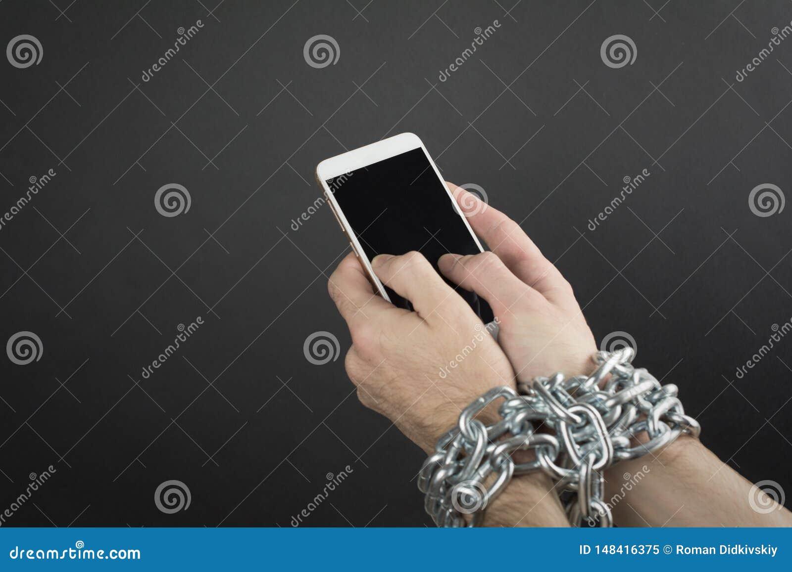 Man hand is gebonden met een ketting aan smartphone