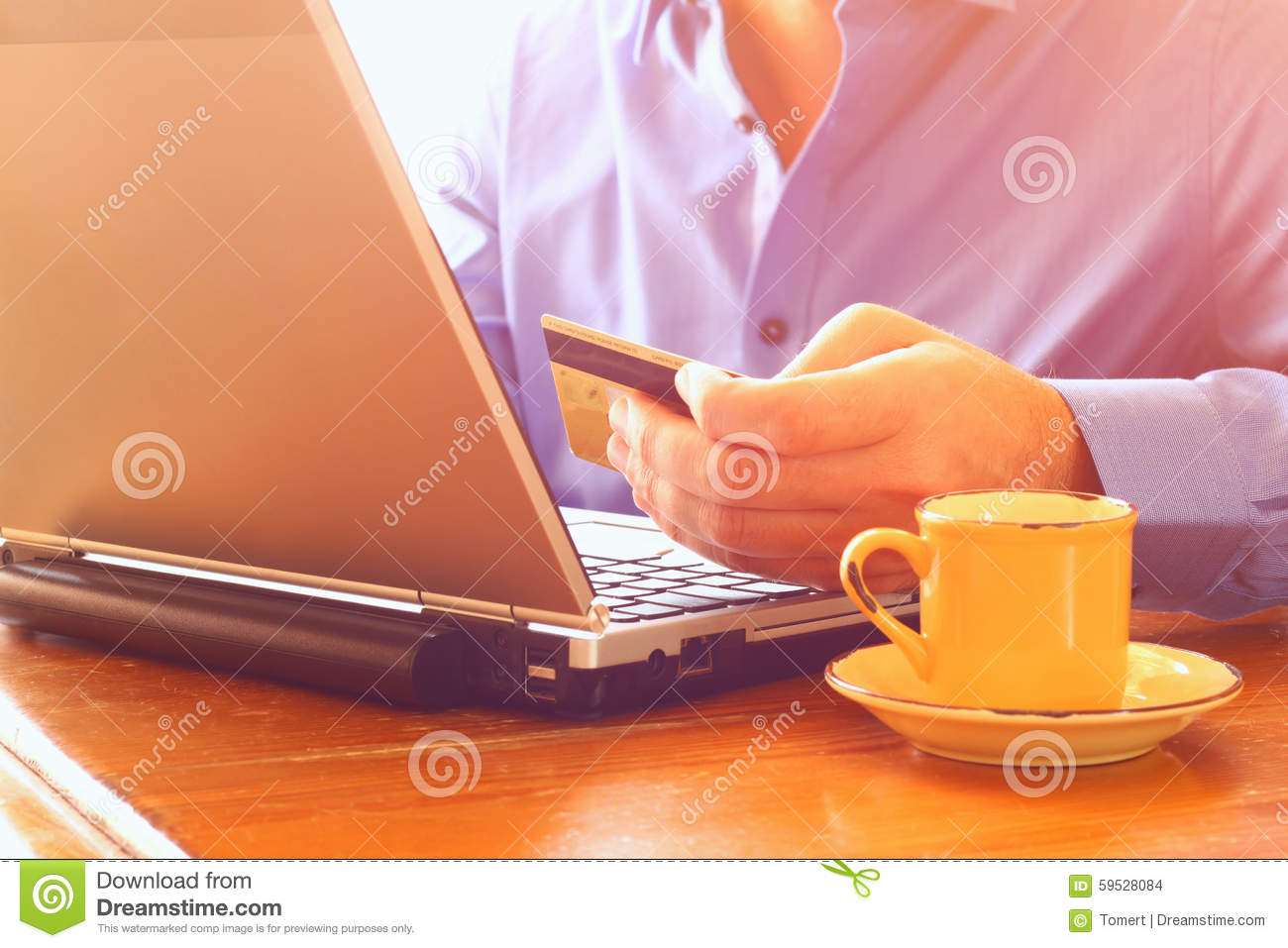 Man Hand Holding Credit Card Next To Laptop And Cup Of
