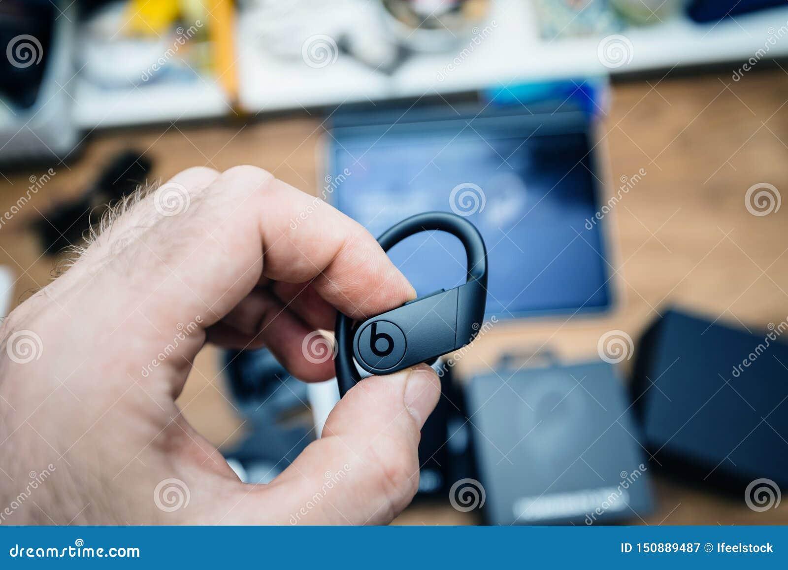 Man hand holding Powerbeats Pro headphone with logotype insignia