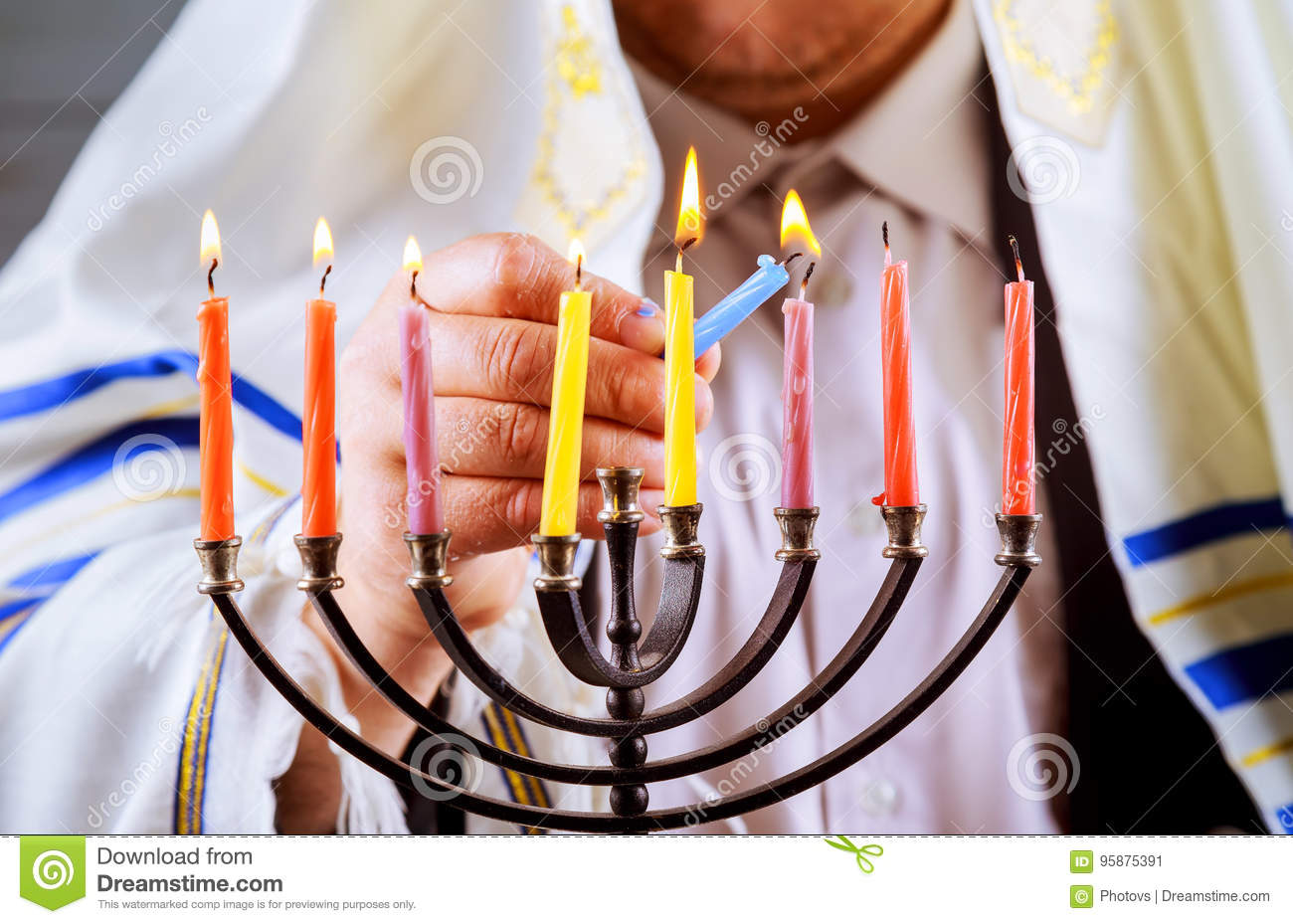 man hand lighting candles in menorah table served for Hanukkah