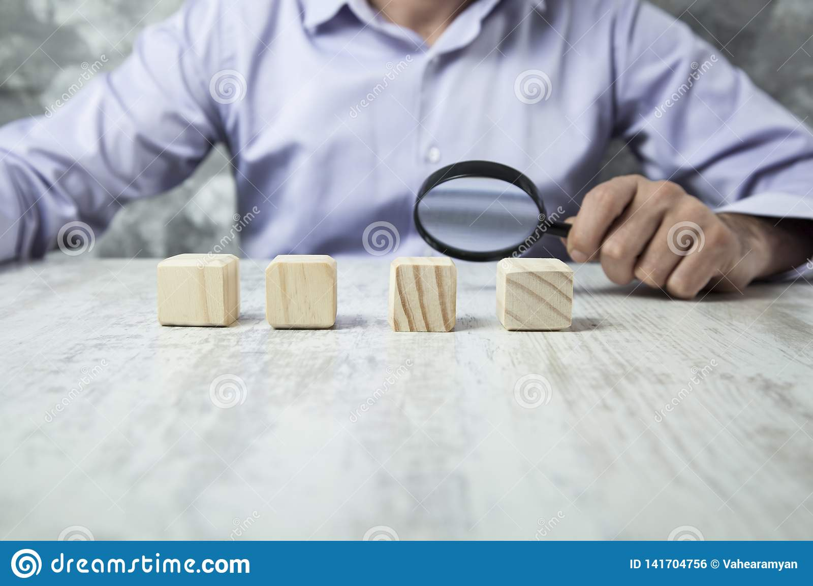 Man hand magnifier with wooden cubes
