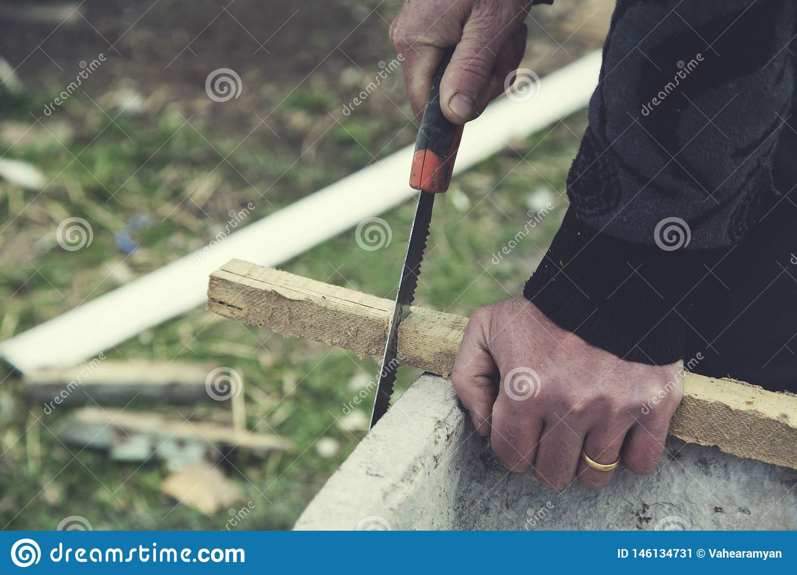 Man hand saws with wood