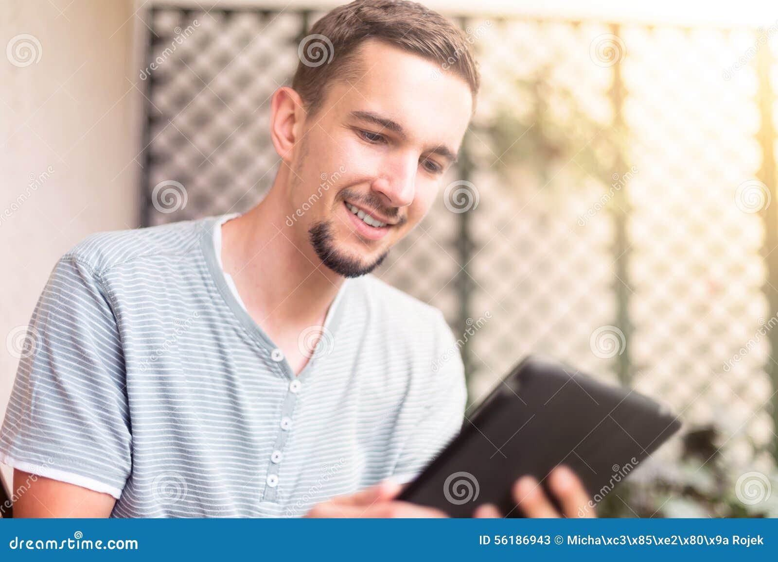 Man hand using white tablet in the garden