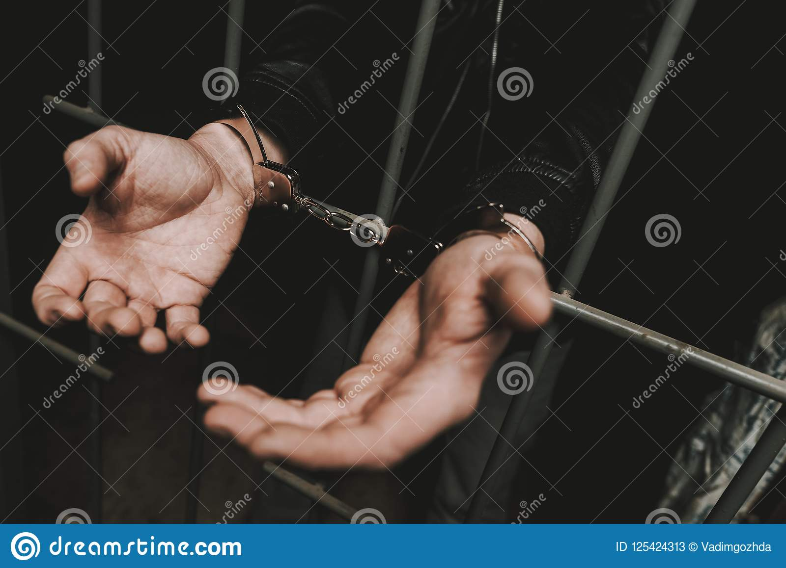 Man In Handcuffs Behind Bars In A Police Station.