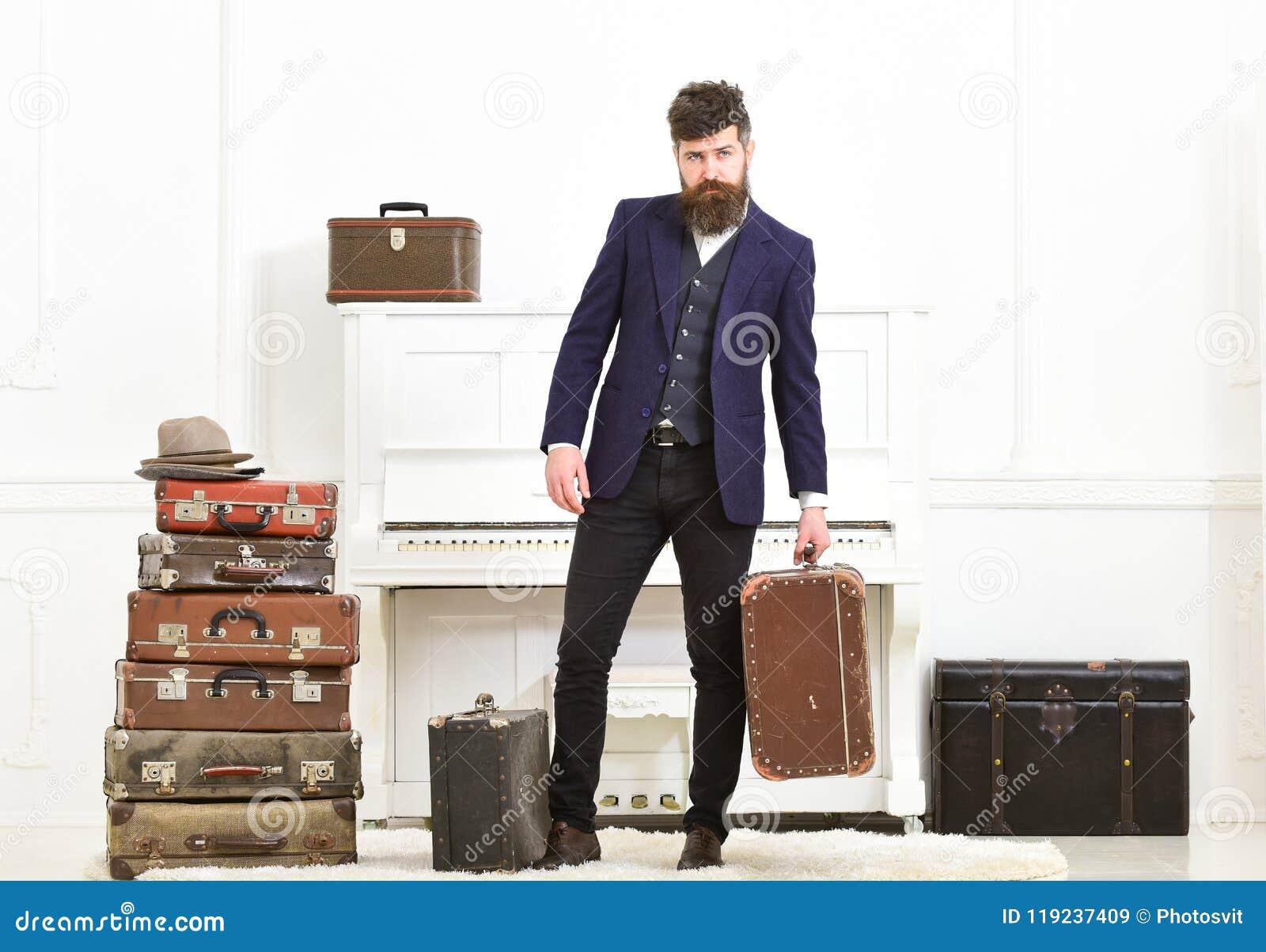 Man, handelsresande med skägget och mustasch med bagage, lyxig vit inre bakgrund Macho elegant på strikt framsida