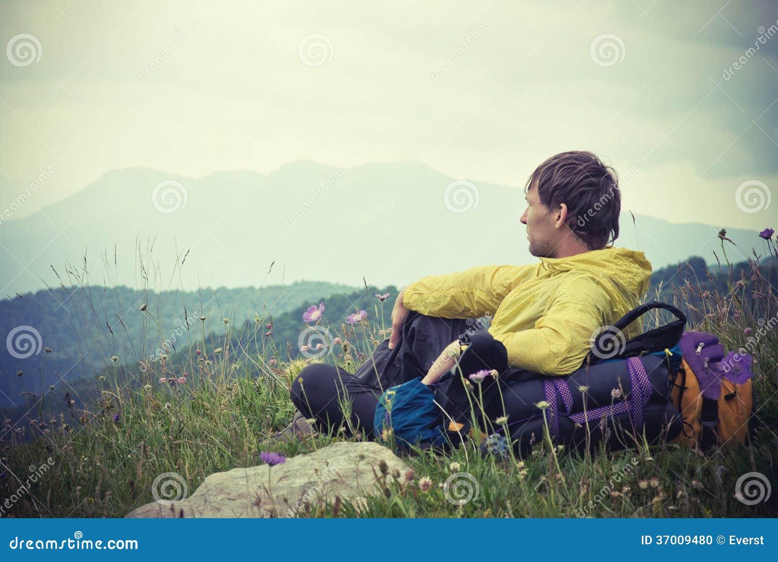 Man handelsresanden med ryggsäcken som kopplar av med berg på bakgrund