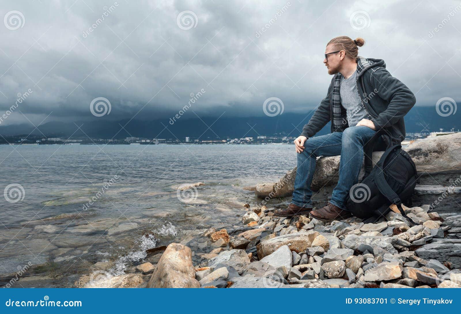 Man handelsresanden med seets för en ryggsäck på kusten mot en bakgrund av moln och ett bergskedjabegrepp av att fotvandra