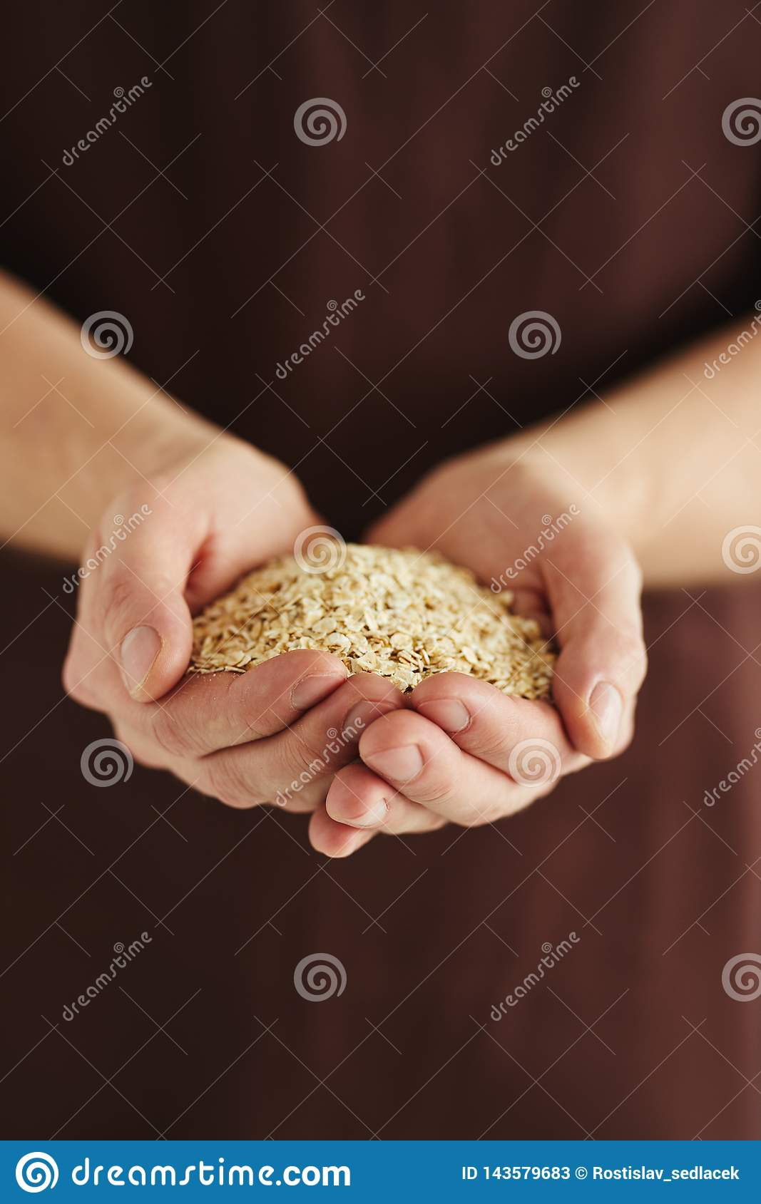 A man with a handful of oat flakes