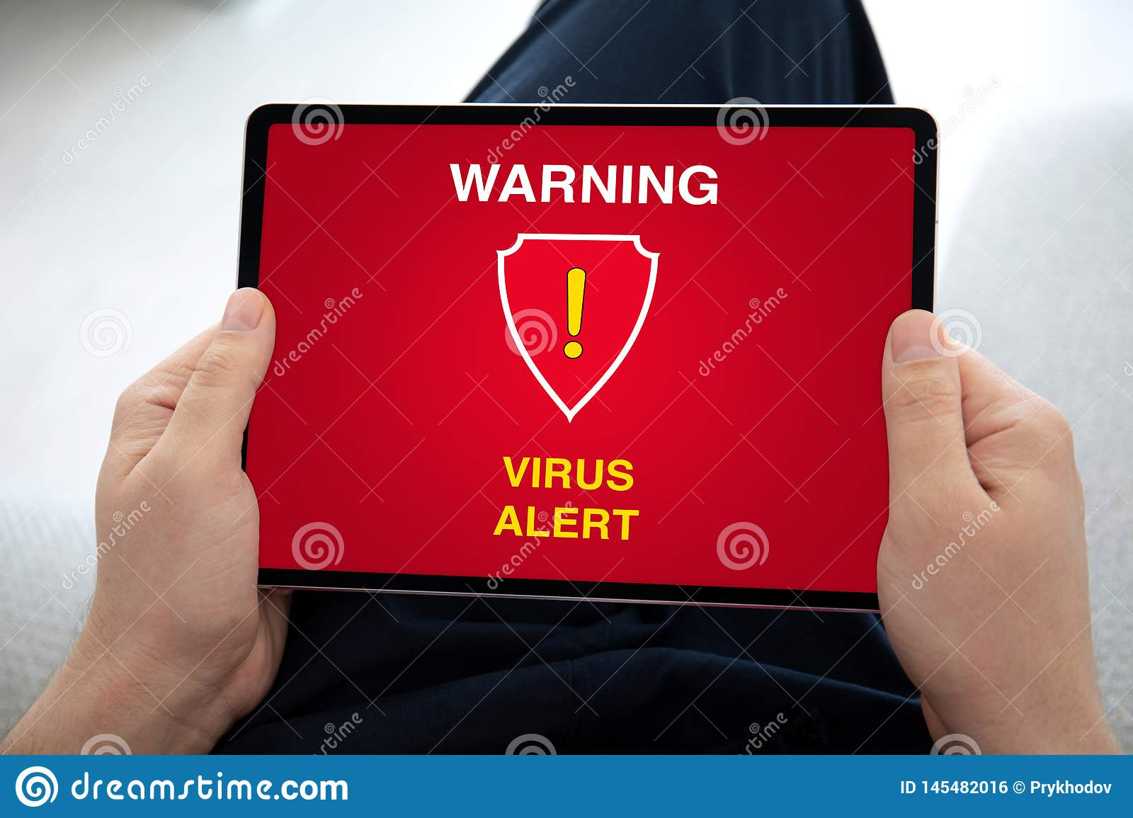 Man hands holding computer tablet with warning virus alert