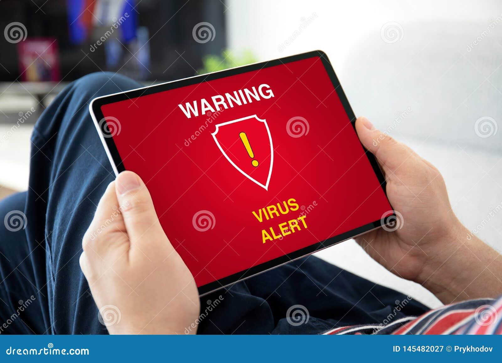 Man hands holding computer tablet with warning virus alert