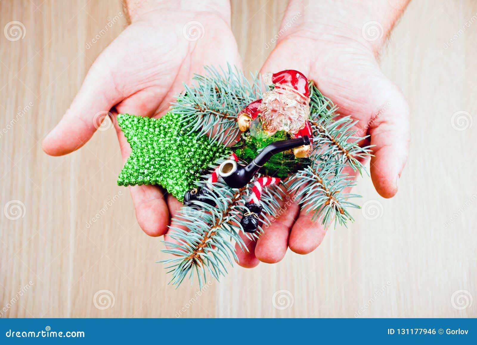 Man hands new year toys Santa Claus fir tree smoking pipe
