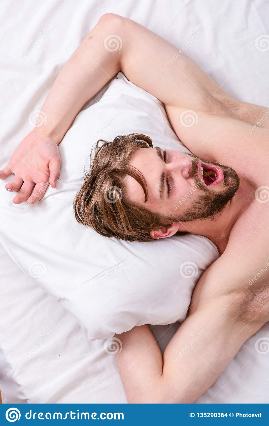 Man handsome guy lay in bed. Get adequate and consistent amount of sleep every night. Expert tips on sleeping better