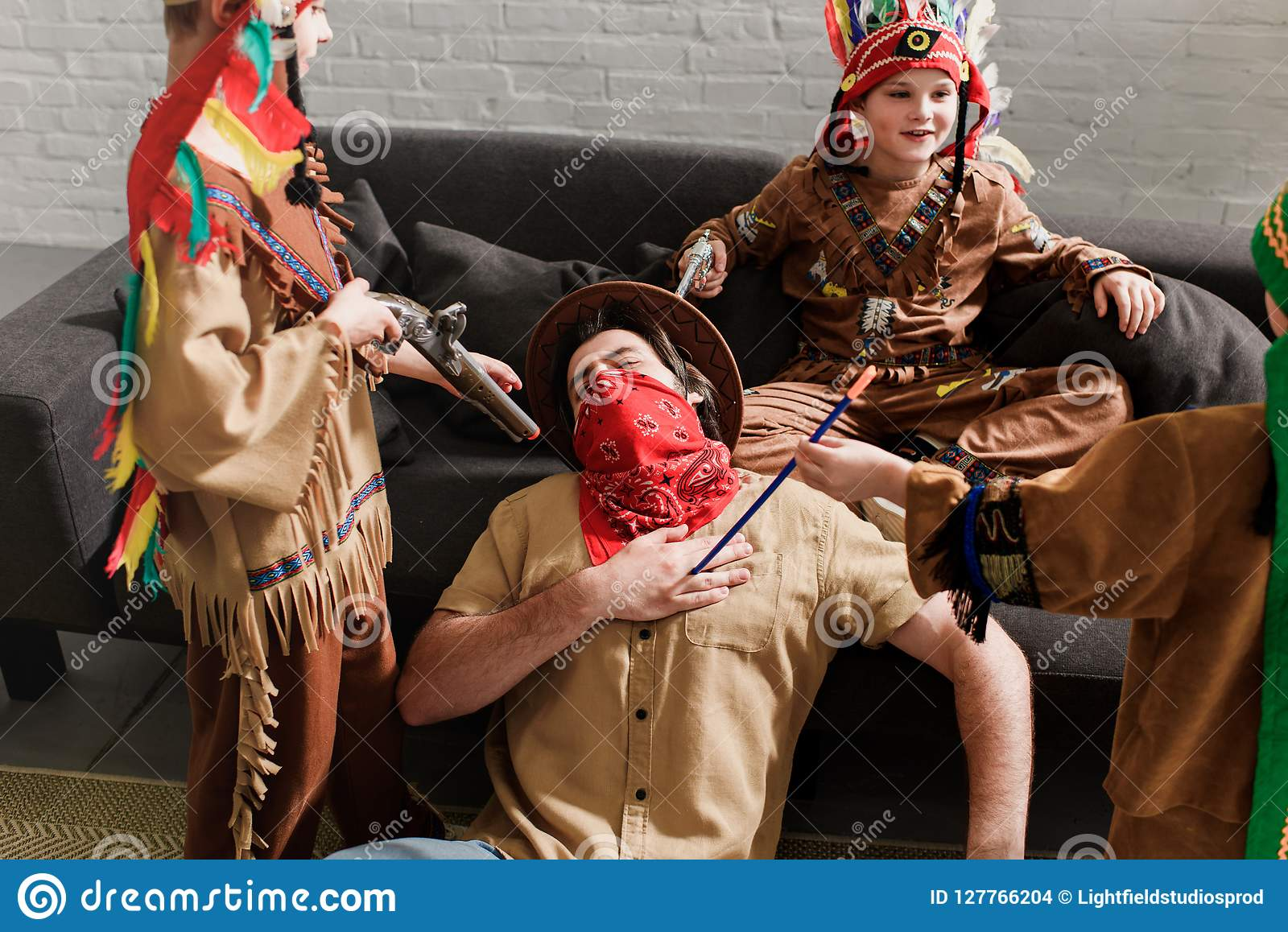 Man In Hat And Red Bandana Playing Together With Sons In Indigenous