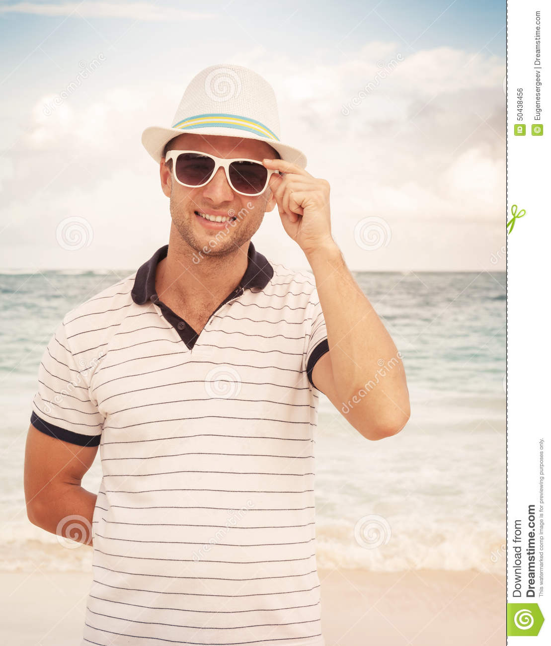 Man in hat and sunglasses standing on the ocean coast